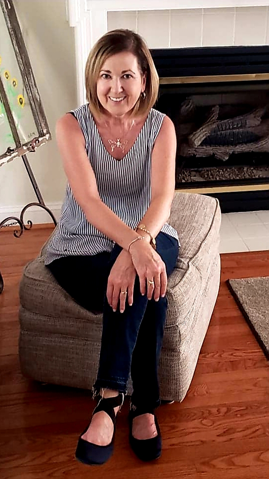 Norma Myers sitting on footstool smiling at camera