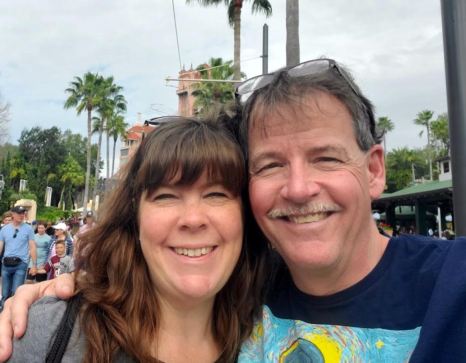 David Grant and his wife smiling at camera
