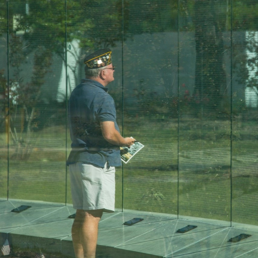 A veteran reads the Glass Wall containing the names of 58,229 Americans killed during the Vietnam War. Vietnam Veterans Recognition Day, Onslow Vietnam Veterans Memorial, Lejeune Memorial Gardens, Jacksonville, NC, 4.27.19. Photo by USMC LCpL Isaiah Gomez