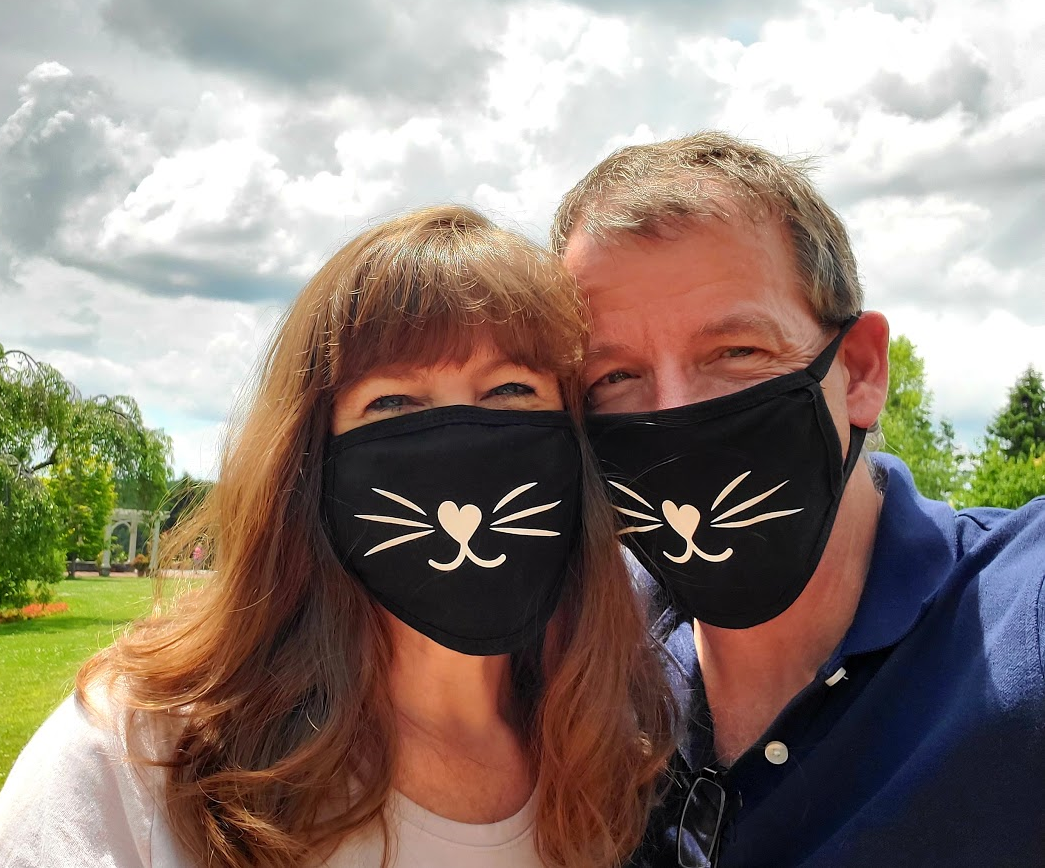 David Grant and his wife wearing black face masks.