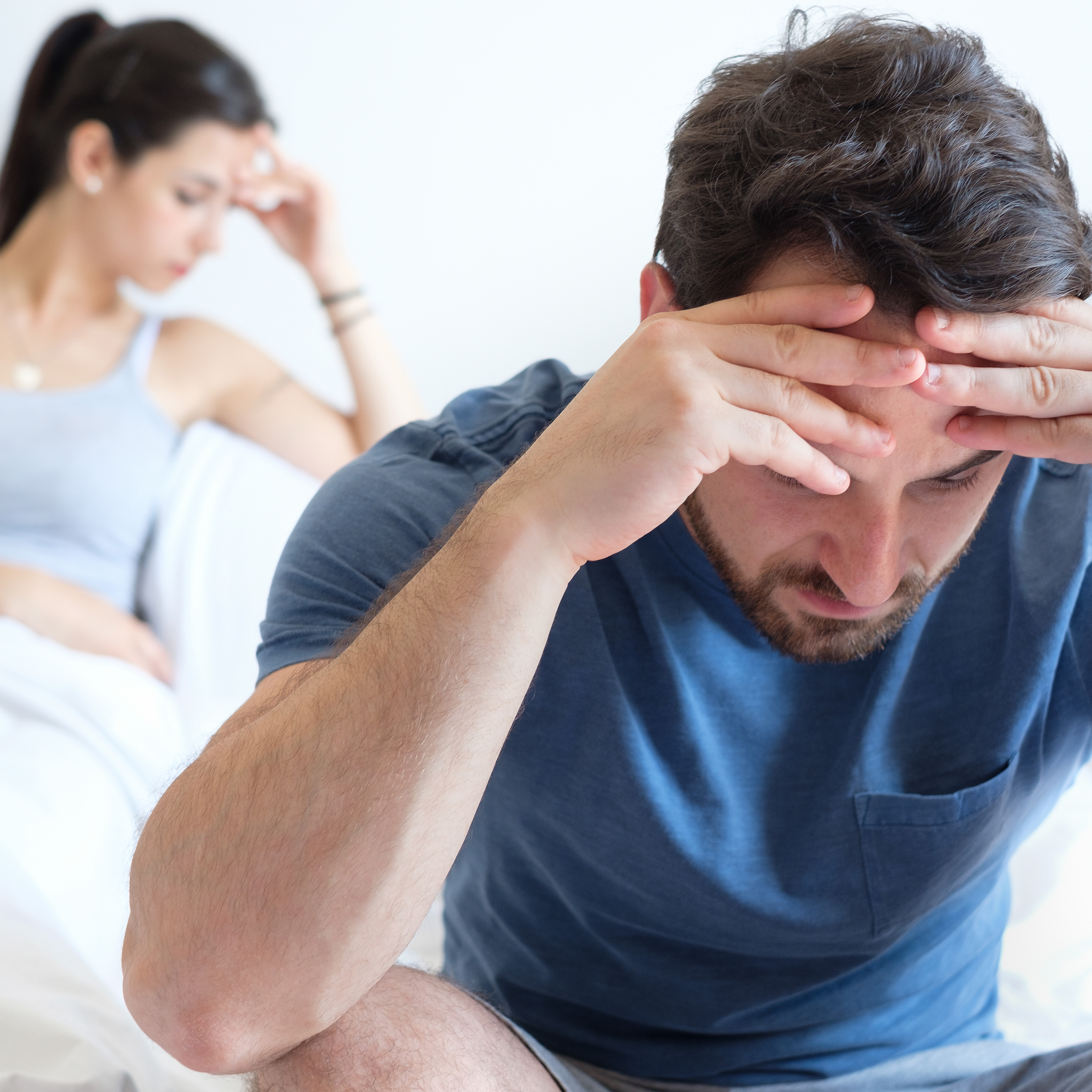 man and woman sitting on bed looking frustrated