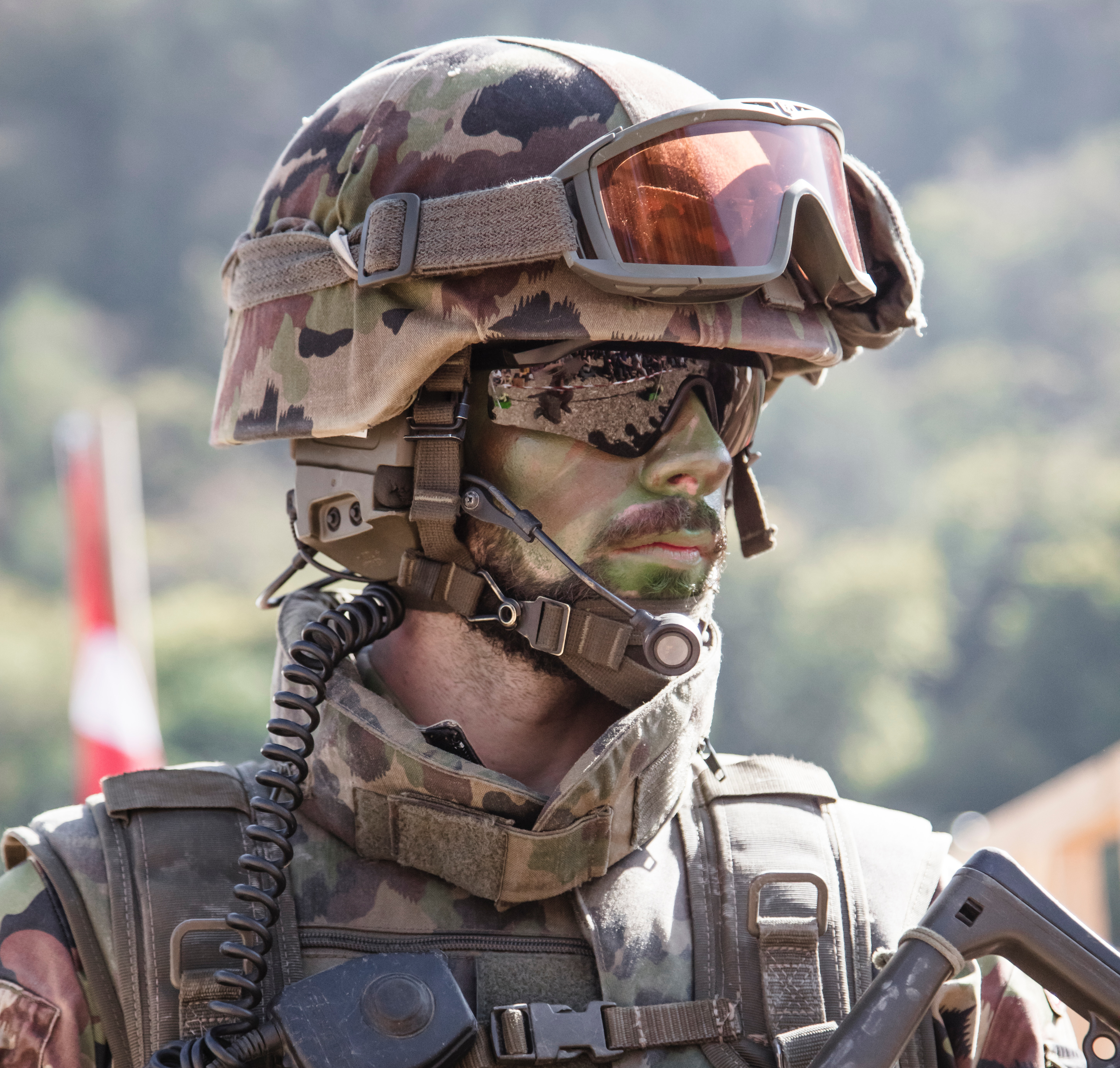 soldier in full camo gear including helmet and goggles