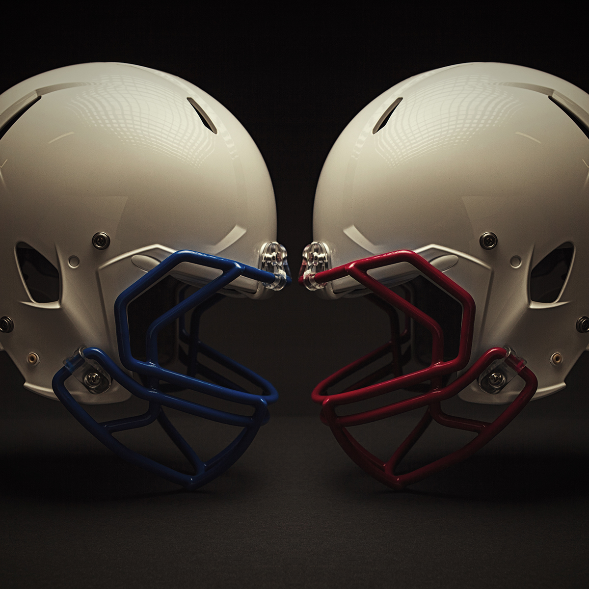 Two football helmets leaning against each other at the forehead.