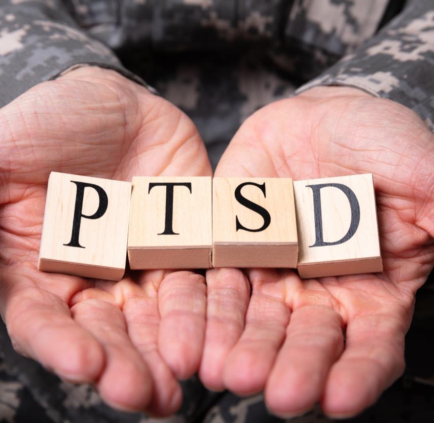 Man holding tiles that spell PTSD in his palms.