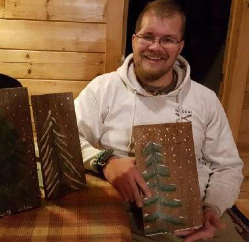 Taylor Bingaman with plaques showing pine tree carvings