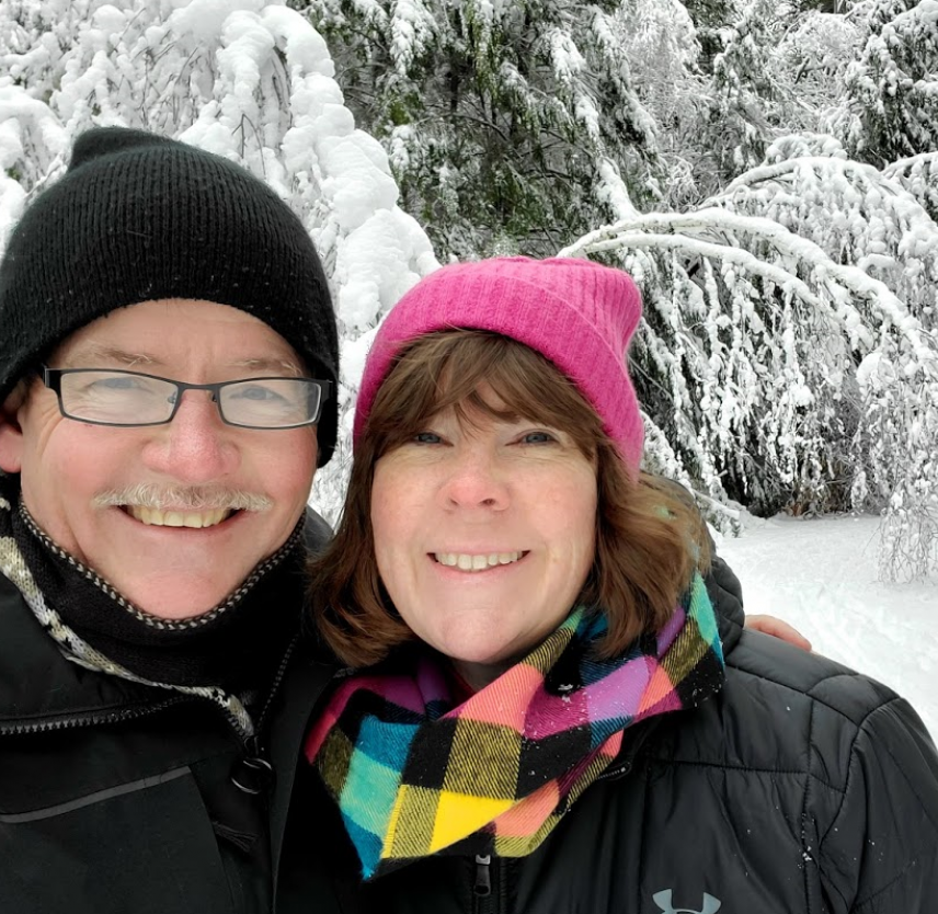 David Grant and his wife smiling at the camera, surrounded by snow.