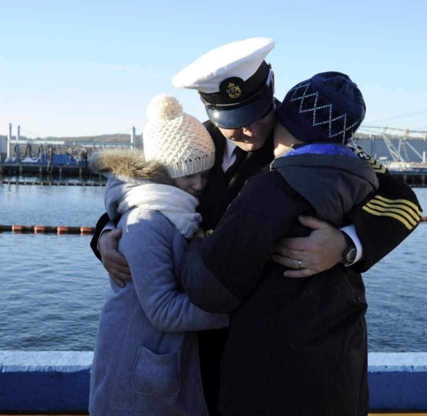 A US Navy Chief Machinist's Mate greets his family after returning home. (U.S. Navy photo by John Narewski/Released)