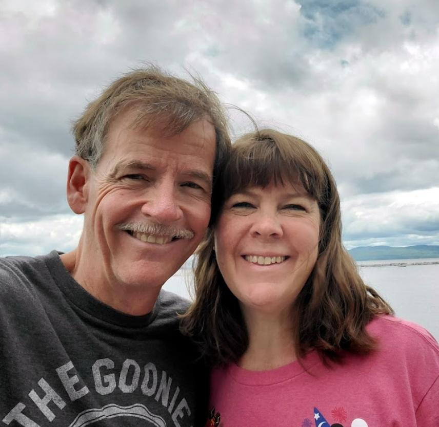 David Grant and his wife smiling in front of a cloudy sky over a body of water