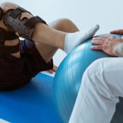 A leg in a brace is pushing against a blue ball that someone is holding.