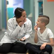 Woman in white lab coat illustrating speech sounds to a boy.