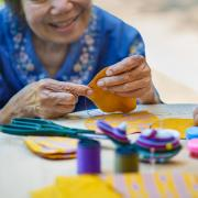 An elderly woman working on needle crafts.