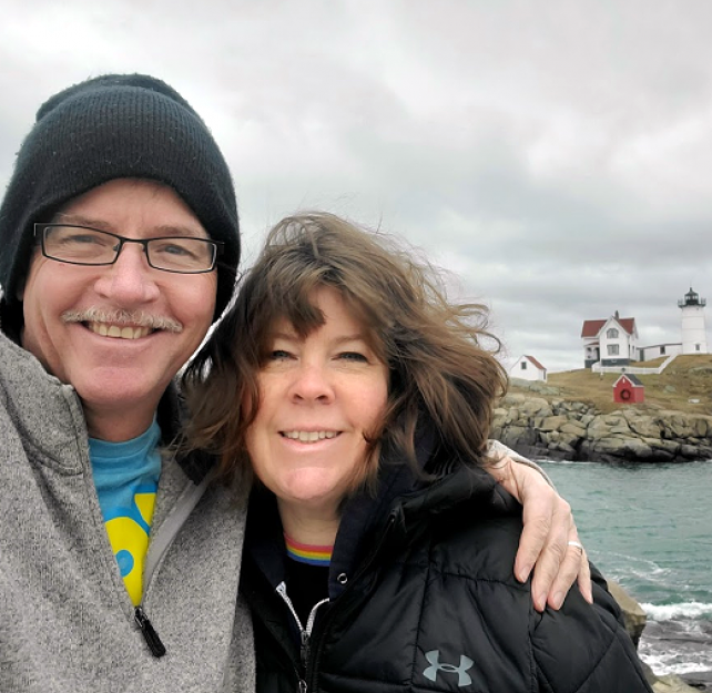 David Grant and his wife smiling at the camera in front of a lighthouse