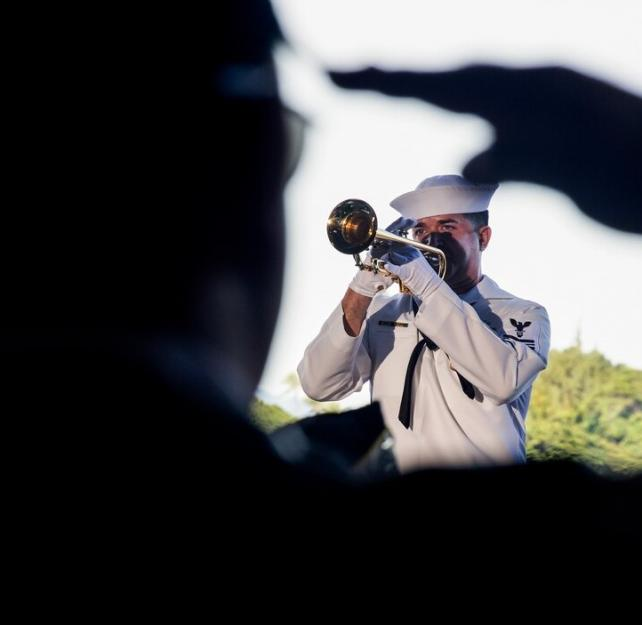 Navy Petty Officer 1st Class Brandon Barbee performs taps during a 75th commemoration event of the attacks on Pearl Harbor at Joint Base Pearl Harbor-Hickam, Hawaii, Dec. 7, 2016. Navy photo by Petty Officer 2nd Class Laurie Dexter.