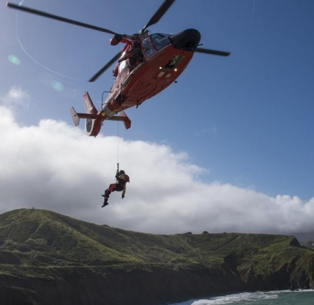 Aircrew members from Coast Guard Air Station San Francisco lower a rescue swimmer towards the cliffs of Mori Point in Pacifica, CA, during vertical surface cliff rescue training, 4.16.2019. U.S. Coast Guard photo by Petty Officer 2nd Class Jordan Akiyama.